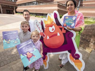 Fynn Flanagan, who created Wheezy and Sneezy, the Flu Twins, and his sister Ayla, who helped inspire Lord Fever, with the City of Wolverhampton Council's Cabinet Member for Public Health and Wellbeing Councillor Jasbir Jaspal and Wolverhampton's Director of Public Health, John Denley