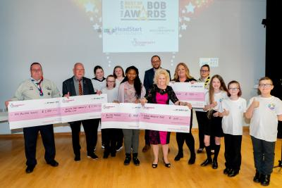 Some of the winners of Bilston's Dragons' Den are awarded their cheques by John Goodman, The National Lottery Community Fund Midland Funding Officer (back, centre) and HeadStart's mini ambassadors