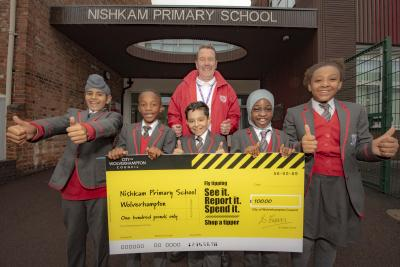 Kevin Finch, site manager pictured with the giant cheque and year 5 and 6 students at Nishkam Primary School Wolverhampton