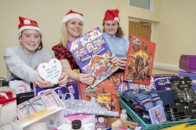 Service manager Laura Wood and young people Chloe Sheldon and Bethany Cureton with some of the hundreds of gifts and advent calendars which have been donated for care leavers and their children
